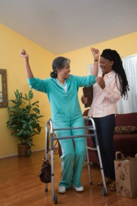 A health care worker helps a woman use her walker